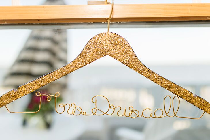 "A handcrafted ""Mrs. Driscoll"" was shaped in gold wire and attached to the bride's glittery wedding dress hanger. The dazzling hanger matched several of the other glamorous gold glitter accents and served as a sweet keepsake for the bride."