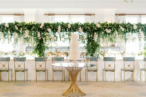 Cake on Gold-and-Glass Table in Front of Greenery-Accented Reception Tables