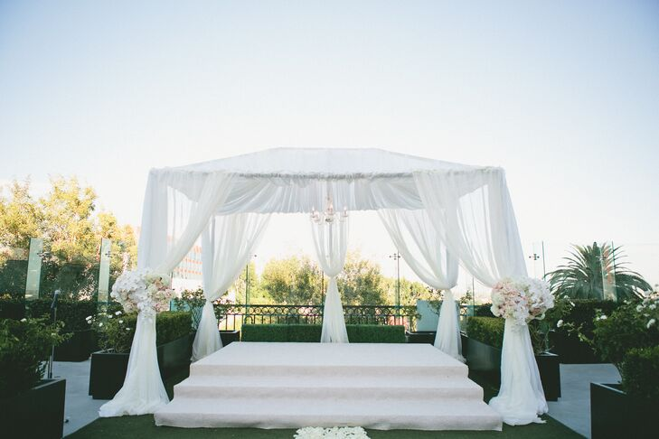 At the end of the rose-petal lined aisle stood a four-post wedding arch draped in airy white fabric and accented with two ornate arrangements of brilliant white orchids and soft pale pink garden roses and peonies.