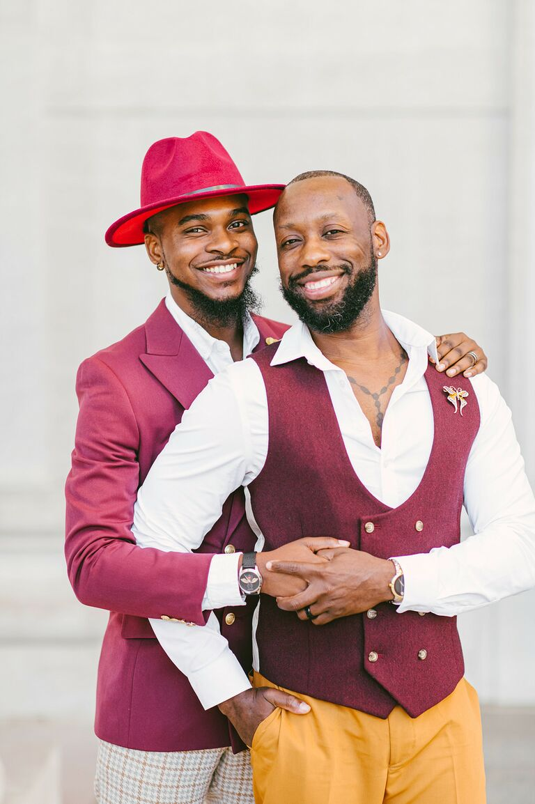 Grooms wearing burgundy suits and holding hands