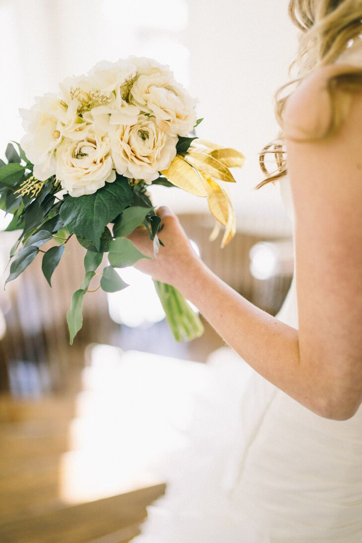 Elena used faux ivory-colored roses and eucalyptus leaves to create her bridal bouquet. The arrangements, including the groomsmen's boutonnieres were made ahead of time and kept their fresh-looking appearance all day and night.