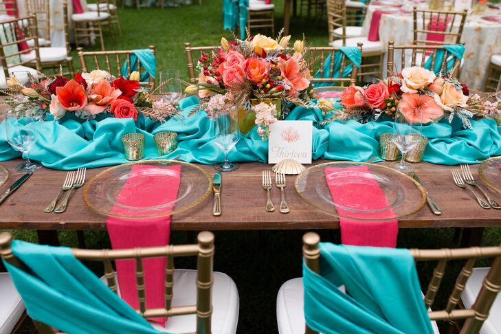 The long farm tables at the reception were decorated with turquoise runners around three teal vases filled with pink flowers. The gold mercury glass votives added plenty of romance to the space. Madeline and Joe loved the contrast between the glam details and the rustic tables, which perfectly completed the Southern aura they were going for.