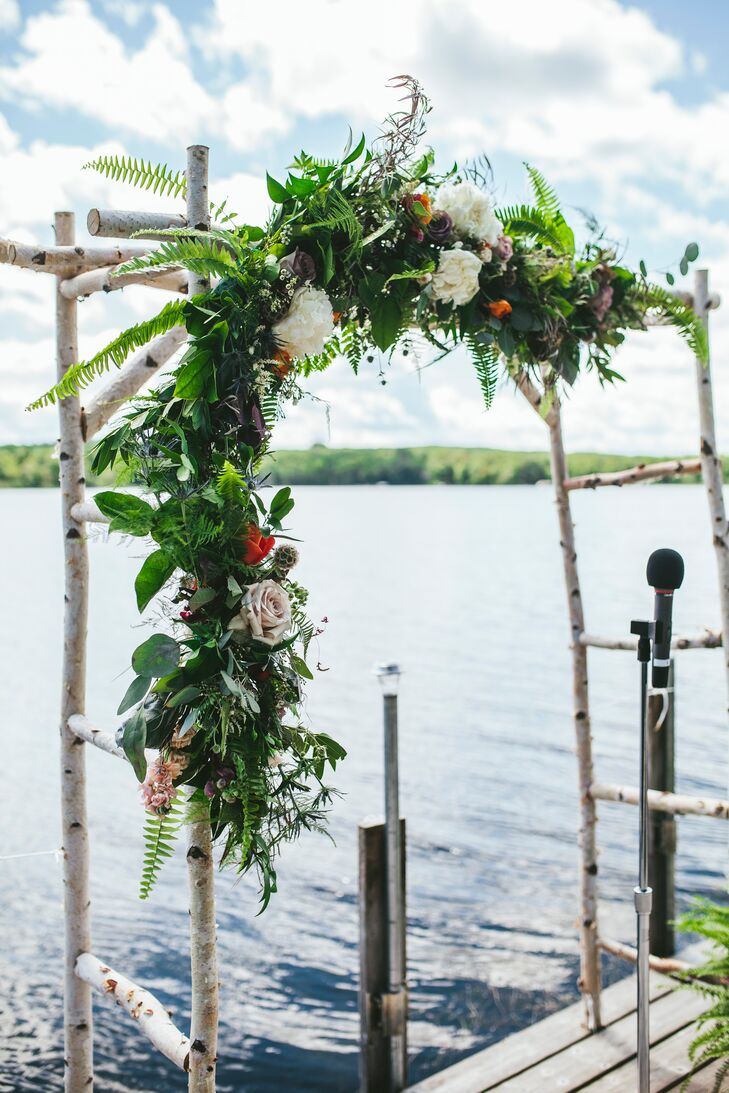 The ceremony was held on the dock, with a birch altar wrapped in flowers and greenery. The photographer shot ceremony photos while wearing waders in the lake.