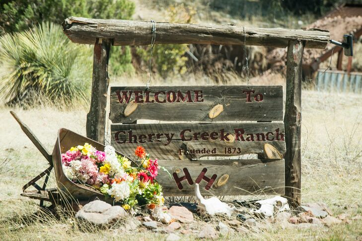 This rustic wooden sign welcomed guests to the venue with bright floral arrangements.