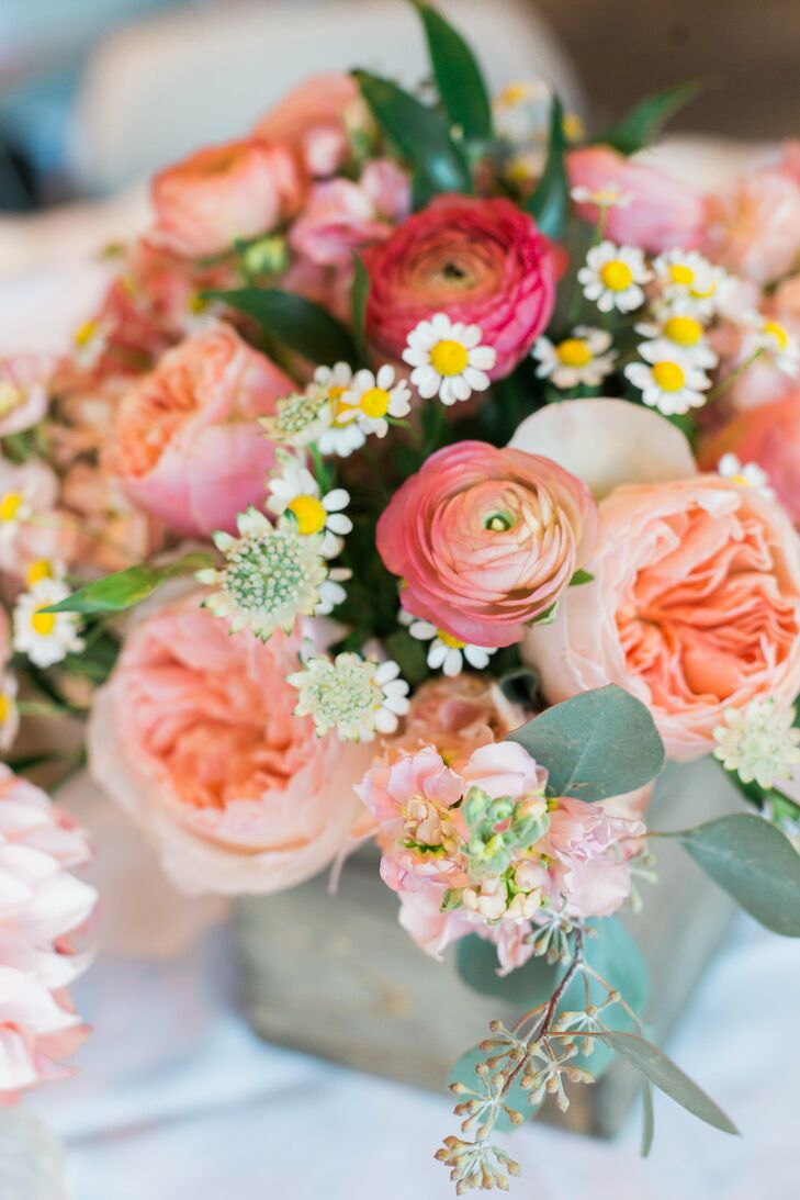 Pink garden roses were paired with daisies and pink ranunculus to create each romantic centerpiece.