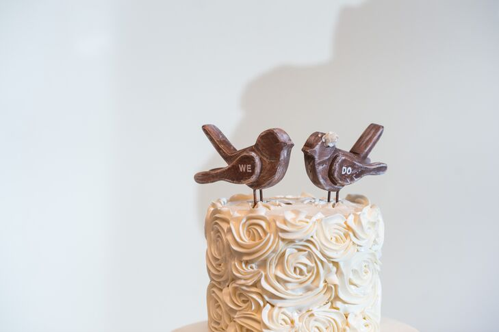 "The couple's wedding cake fit both their shabby-chic theme and fall wedding date! The Bake Works filled the confection with pumpkin cake and covered the tiers in piped ivory swirl accents or classic fondant. ""It was a big hit!"" says Miriam. They topped the confection with two exposed wood lovebirds."