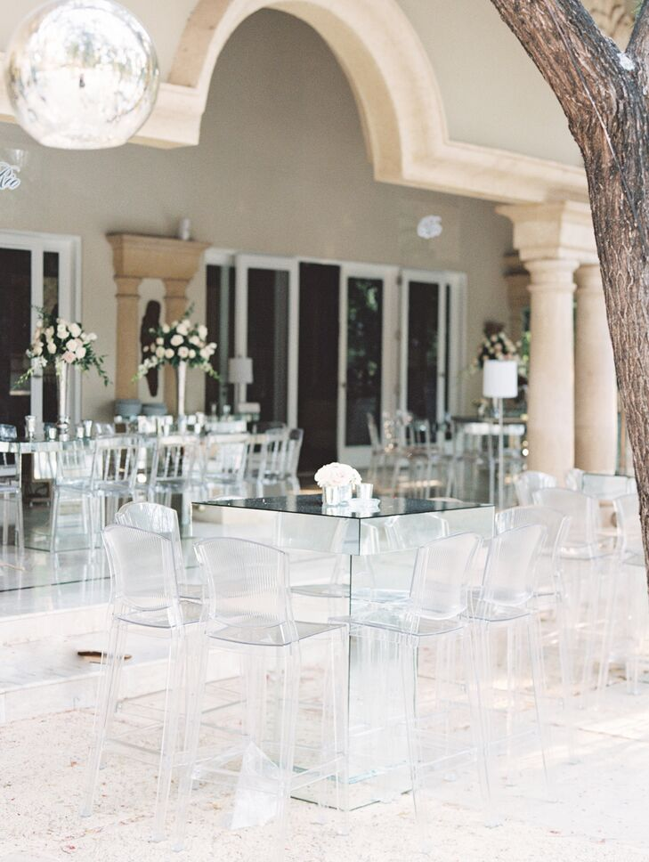 At the classic-meets-modern reception at Monique's family home, clear chairs and mirrored tables provided a chic, airy setting.