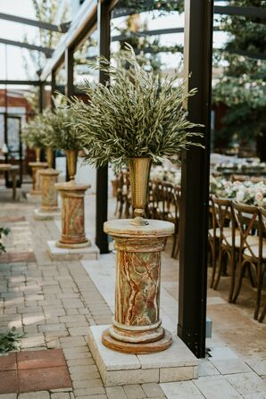 Greenery Arrangements in Gold Vases Atop Marbled Pillars