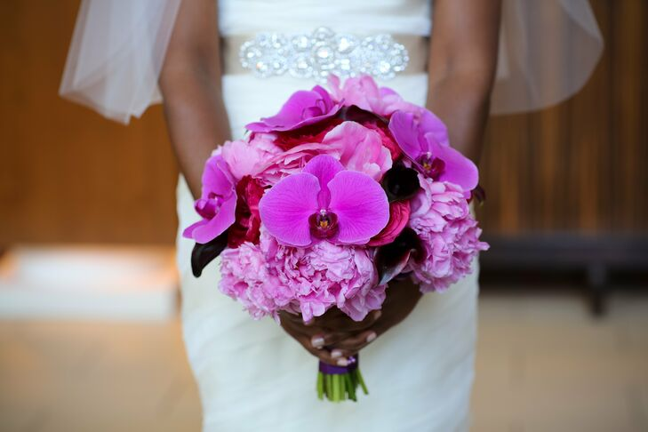 A lush, clutch-style bouquet of fuchsia and dark pink blooms was mixed in with deep eggplant calla lilies.