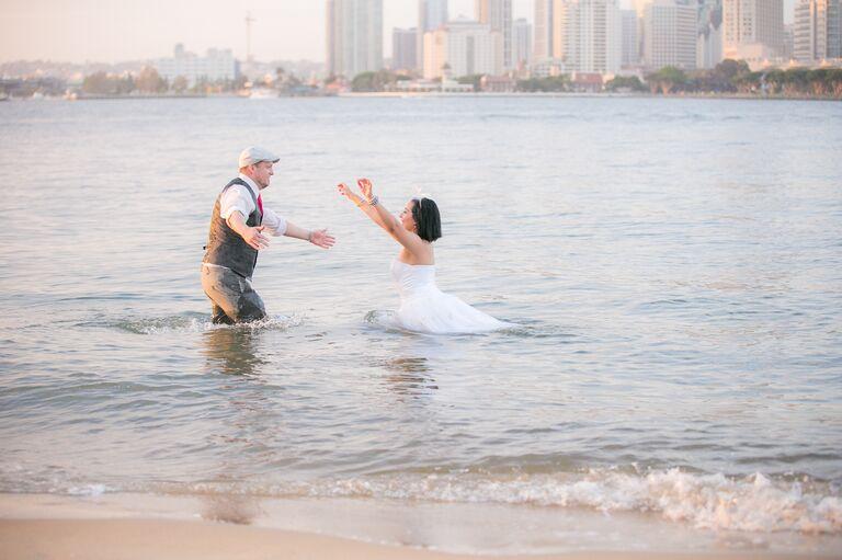 Bride running toward groom in the water