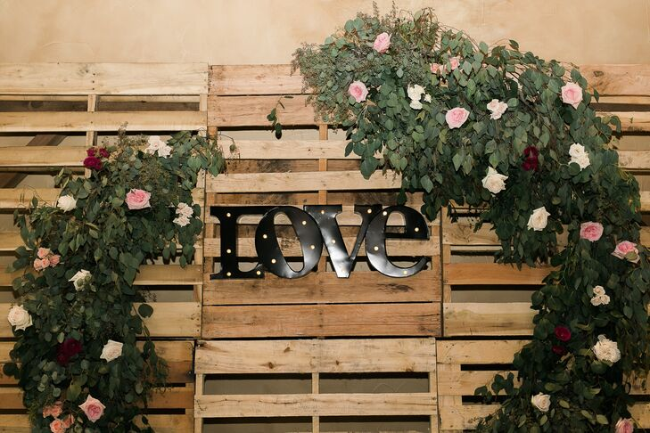 """Brieann's second favorite floral piece (next to her bouquet) was a huge pallet-wood wall decorated with greenery and flowers and an illuminated """"love"""" sign serving as the backdrop behind the DJ. The wall was """"perfect for the background of our dance pictures and video."""""""