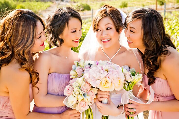 Joanne stood with her bridesmaids wearing pink and purple strapless dresses, and they all held pastel bouquets filled with peonies and roses.