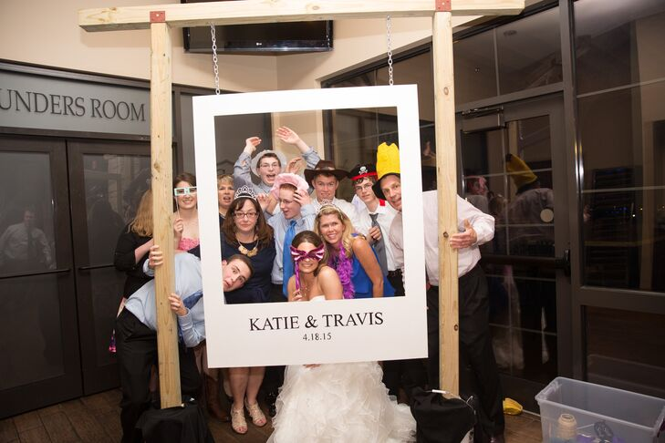 Katie and Travis posed with their wedding guests inside a DIY photo booth prop set, crafted by helpful friends and family members. A large Polaroid template hung from the tall wooden set in the corner of the reception space.