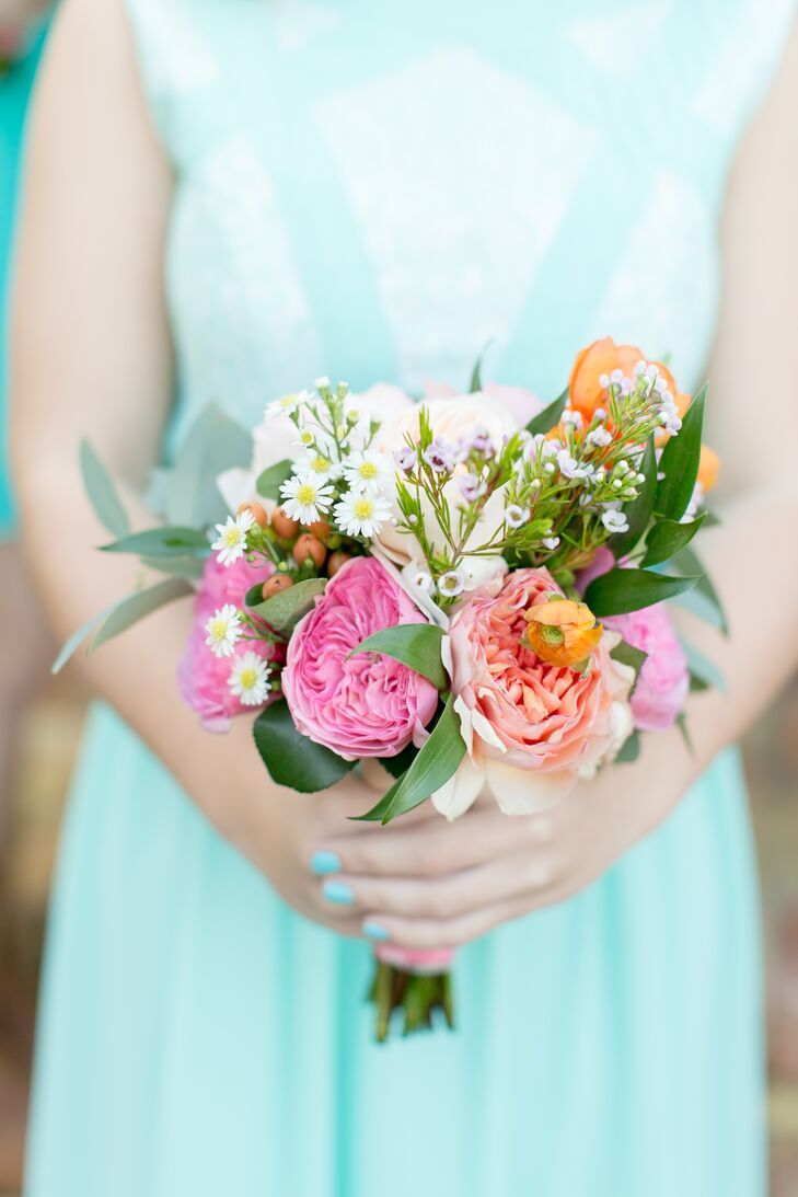 The bridesmaids wore different dresses, but each carried a sweet matching bouquet. Flowers by Lesley filled every arrangement with pink and orange garden roses as well as eucalyptus, greenery, wildflowers and orange ranunculus.