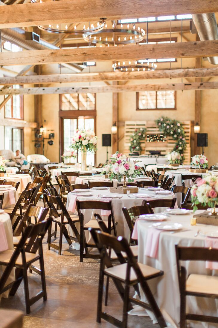 Pink and white linens and pink and white floral arrangements added a chic touch to a rustic room.