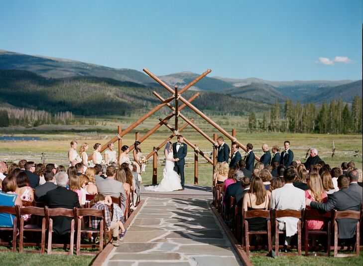"""Nicole and Alex's outdoor wedding ceremony was held beneath a rustic timber arch at Devil's Thumb Ranch. """"We went back and forth on how we wanted to decorate the ceremony site,"""" says Nicole. """"We ultimately decided that we didn't need any decorations at all, the view of the mountains and the ranch is spectacular enough."""""""