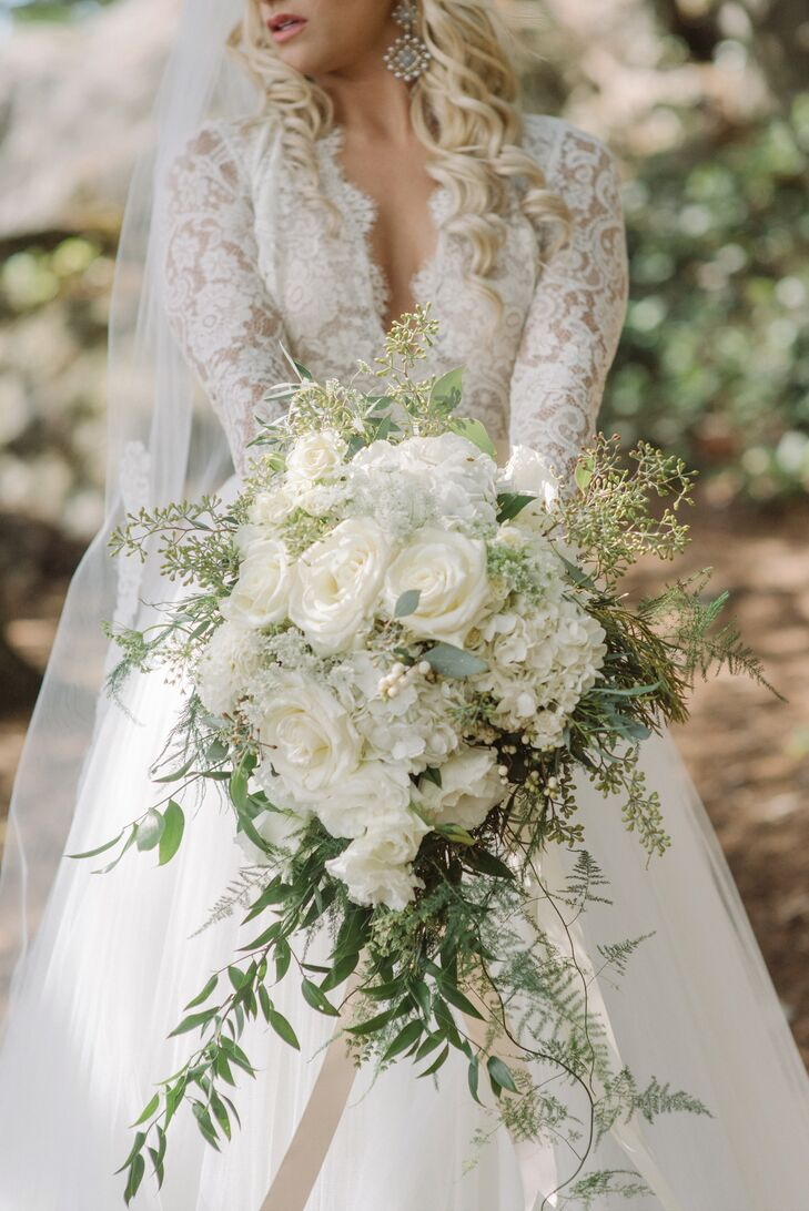 Continuing the romantic theme, Vanessa paired her elegant long-sleeve lace gown with a full bouquet of white roses, hydrangeas, and leafy greenery crafted by Shamay of Flowers by Shamay.