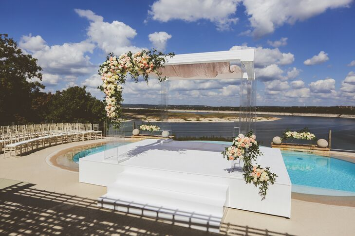 """Samantha always dreamed of having her wedding at her parents' home on a high cliff overlooking the picturesque Lake Travis in Austin, Texas. """"The home itself is elegant and inviting, not to mention all of the warm and loving memories Brennan and I have there with family and friends."""" The platform built over the hot tub held a chuppah adorned with roses, hydrangea and orchids."""