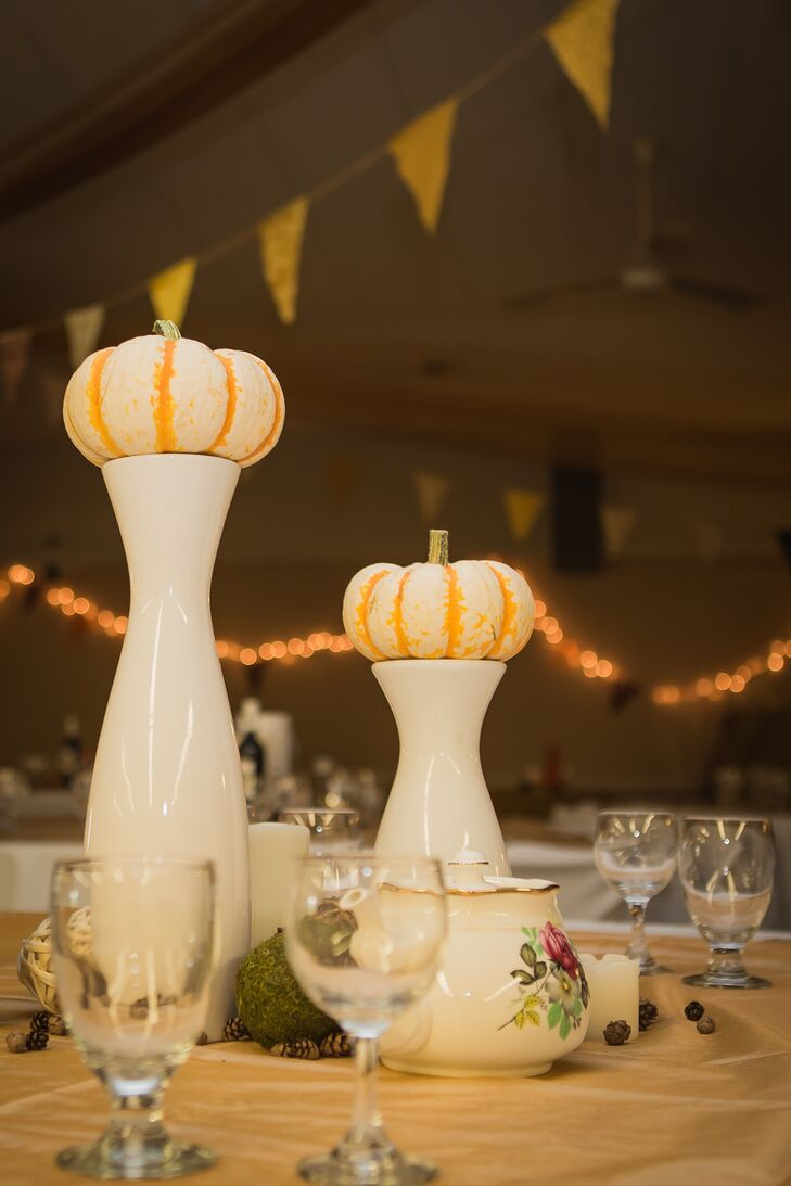 Small pumpkins were placed on top of white vases for the rustic-inspired centerpiece decor.