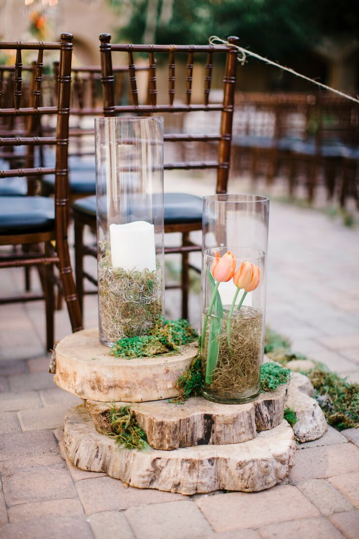 Wooden slabs piled on top of one another had tall glass vases filled with white candles, moss and tulips—bringing a rustic look to the ceremony courtyard space.