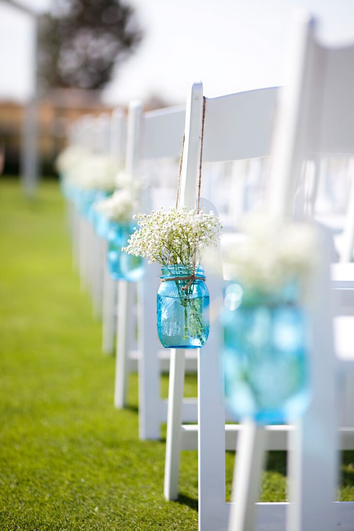 Sara and Kris kept the ceremony decor simple with their aisle decorations—blue mason jars filled with baby's breath that dangled by twine. The decoration also went along with the day's country theme.