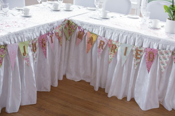 """A """"Just Married"""" bunting sign was strung across the two long head tables at the reception."""