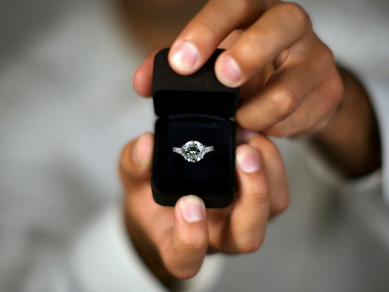 person holding engagement ring box with diamond ring
