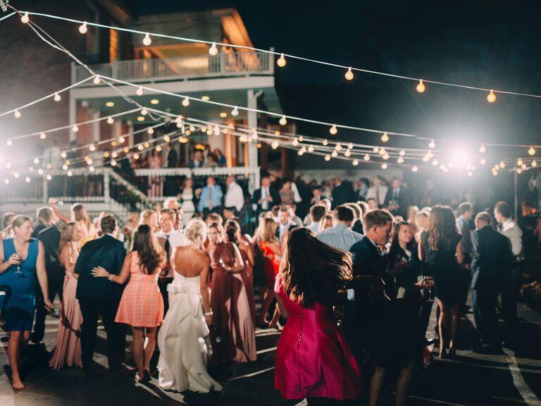 wedding guests dancing outside under bistro lights