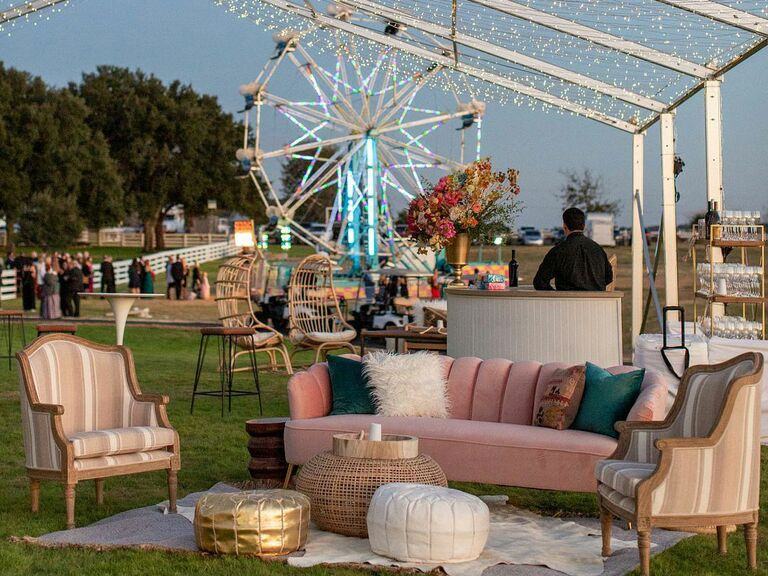 Colorful lounge area with couches and pillows and string lights at outdoor wedding reception