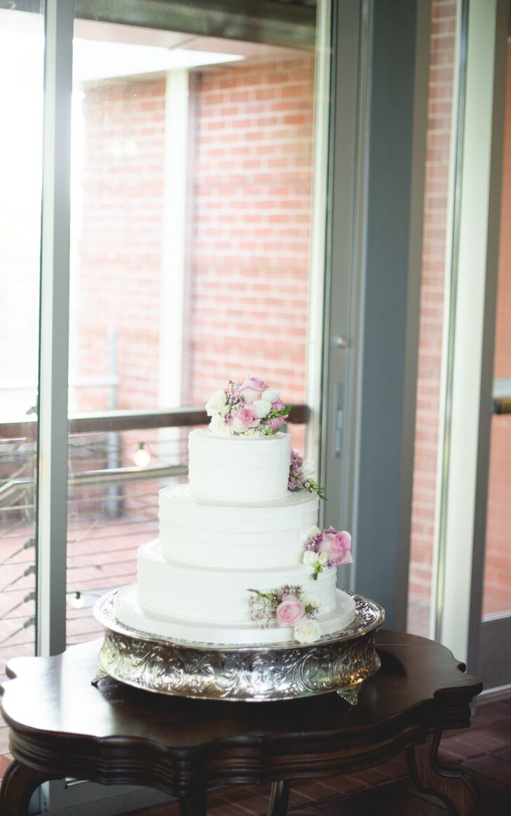 The three tier wedding cake featured textured white buttercream frosting decorated with fresh flowers.