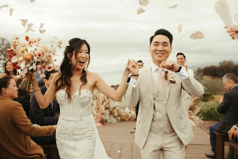 Couple dancing as they exit wedding ceremony amid cascade of flower petals
