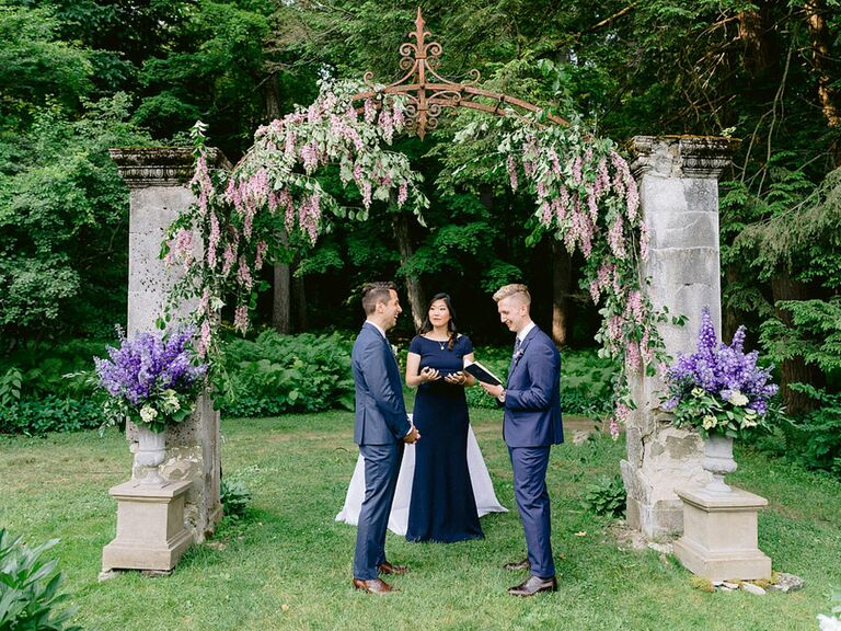 Grooms exchanging vows at outdoor whimsical garden wedding venue with hanging wisteria