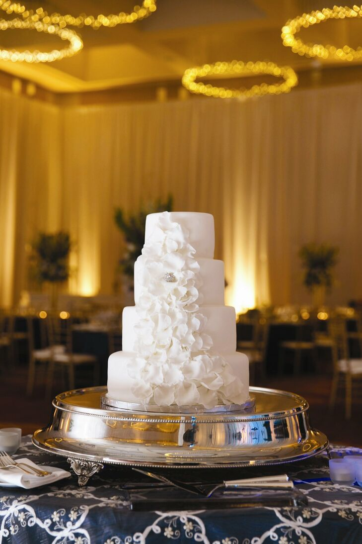 The simple four-tiered fondant cake was decorated with an asymmetric cascade of white sugar flowers and a single crystal accent. Becca and Phil chose a confetti flavor for the cake (her favorite) and also offered a chocolate cake with salted caramel icing (Phil's choice).