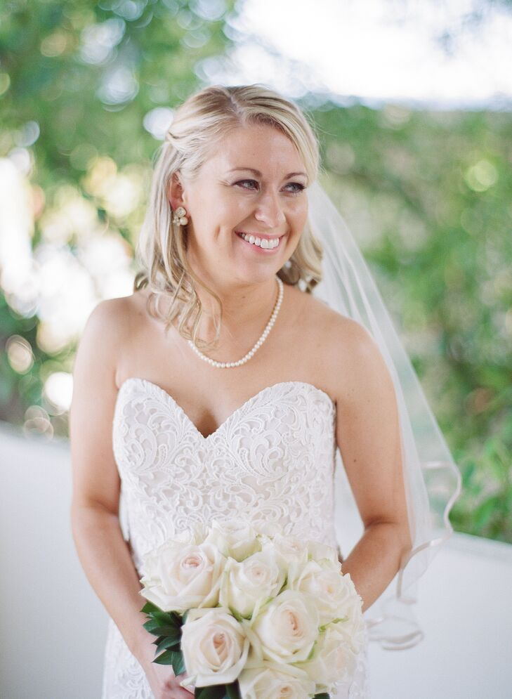 Laura accented her Allure Romance wedding dress with a white rose bouquet, curled down hairstyle and her mother's pearls. The pearls were also worn by Laura's sister on her wedding day, she says.
