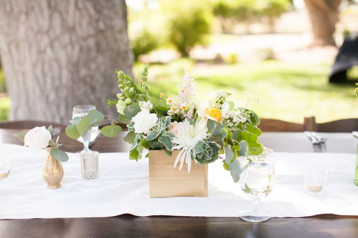"""Dining tables were decorated with flower centerpieces of chrysanthemums and roses accented with greens, arranged inside wooden boxes that contributed to the rustic feel of the wedding. """"We kept the flowers very natural and incorporated a lot of leafy foliage into the arrangements, which were mixed with subtle pops of color,"""" Naomi says."""