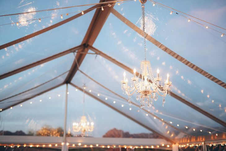 Chandeliers are an unexpected decor element in the outdoor tent.