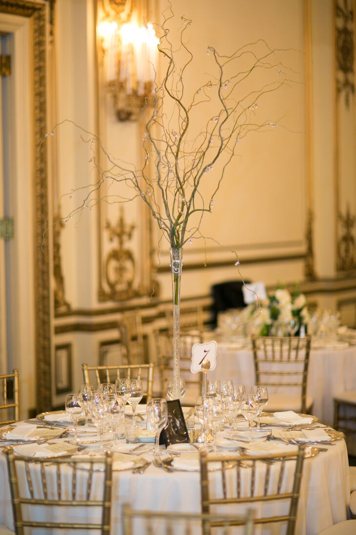 At the reception, dining tables were dressed in ivory tablecloths and decorated with beaded branch centerpieces.