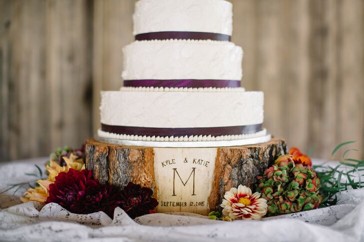 The four-tier cake sat upon a real hand-carved log-slice platform engraved with Katie and Kyle's wedding date. Each layer had a plum ribbon wrapped around the bottom portion and flavors included almond, mixed citrus and chocolate chip cake.