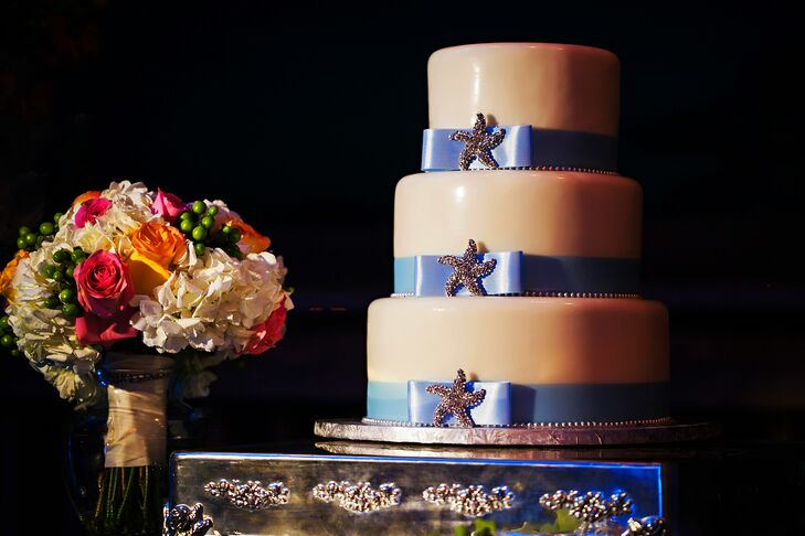 The three tier white cake had a light blue ribbon with a starfish brooch around each layer.
