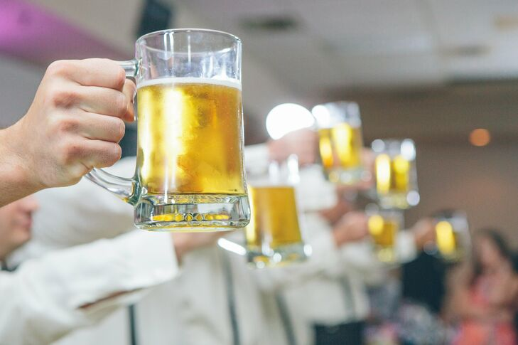 """Instead of a garter toss, Kyle had a stein-holding contest with his groomsmen during the reception at St. Gregory's Armenian Hall in Granite City, Illinois. Good Times Polka Band played """"Beer Barrel Polka"""" as the groomsmen battled it out to see who could hold their pint for the longest amount of time."""