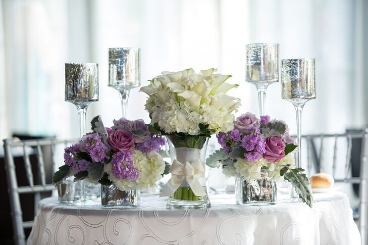House of Flowers created a distinct centerpiece for Ashley and Charlie's sweetheart table. In lieu of the towering cherry blossom-inspired arrangements, the florists displayed two bouquets of purple and white roses, stock and hydrangeas in small square vases, which they styled alongside stemmed mercury-glass votive candleholders. At the center of the arrangement stood Ashley's calla lily and hydrangea bouquet, adding height and a touch of drama to the petite tablescape.