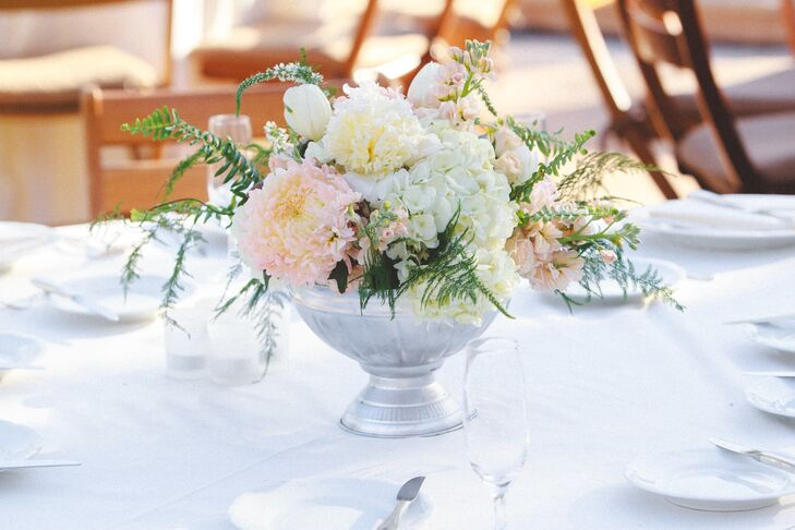 To bring the wedding's romantic theme to life, the florists at Table Tops, Etc. created garden-inspired arrangements of roses, dahlias, peonies and ferns in pale pink and cream hues for the reception, displaying each in a stately silver bowl vase, a touch that introduced an air elegance to the tablescapes.
