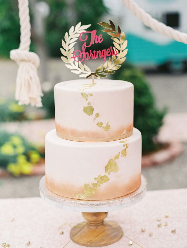 The bride's cake embodied the romantic vibe of the wedding day—a two-tier white cake with gold spattered on the surface. The cake topper depicted Linsay and Stefan's last name in pink, rimmed with a gold wreath design.