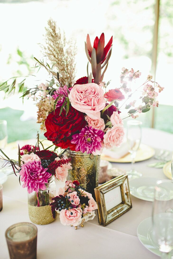 Clusters of vintage vases and mason jars filled with ivory, blush, red and burgundy blooms topped the reception tables.