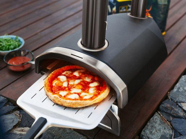 Portable black and silver pizza oven outside with mozzarella pizza