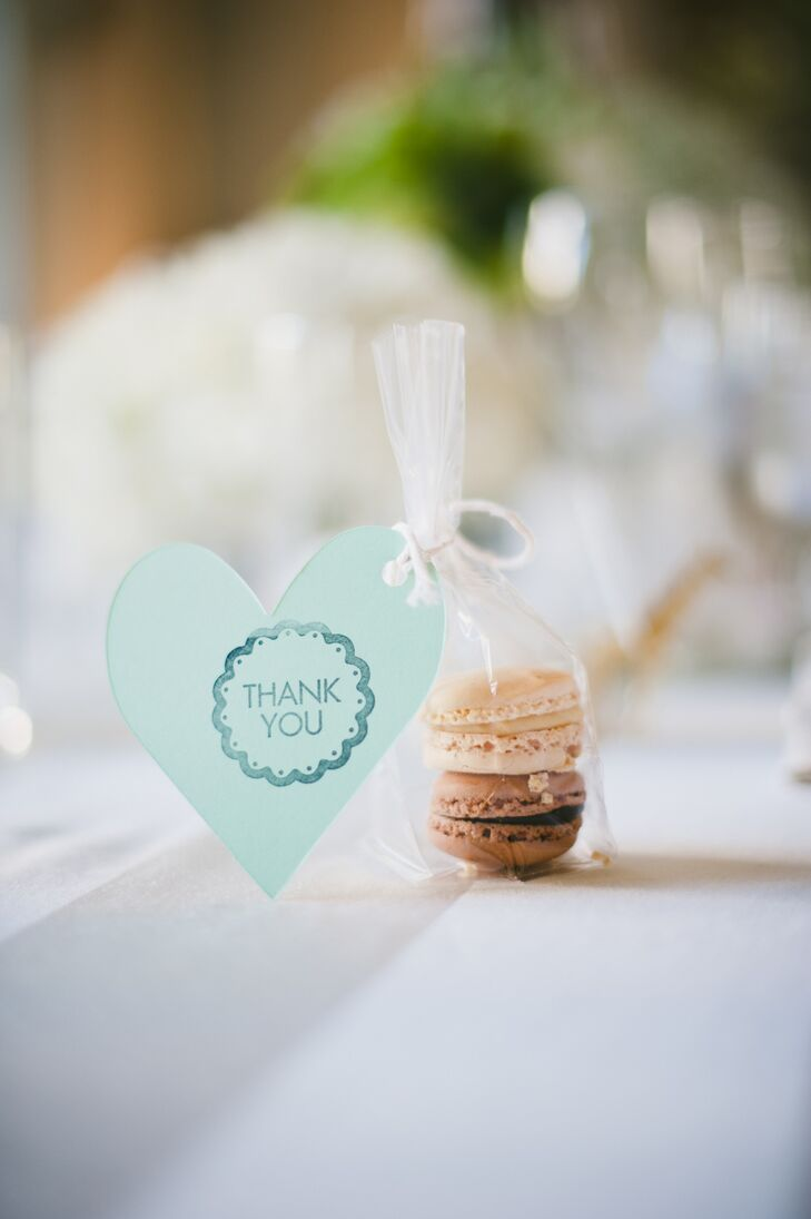 As a thank you to their guests, Margot and Ricky placed small bundles of French macarons tied together with hand-stamped mint green hearts at each guest's seat.