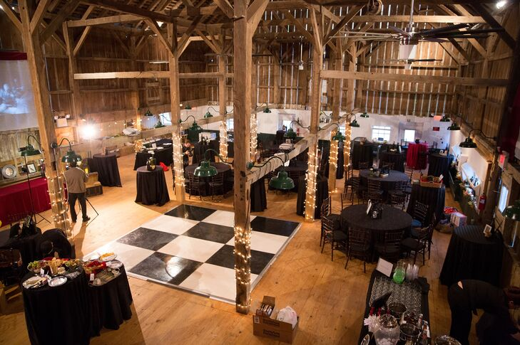 The reception took place in the barn at Worsell Manor. Black dining tables surrounded a checkered black-and-white dance floor, and the barn's wooden beams were wrapped in string lights.