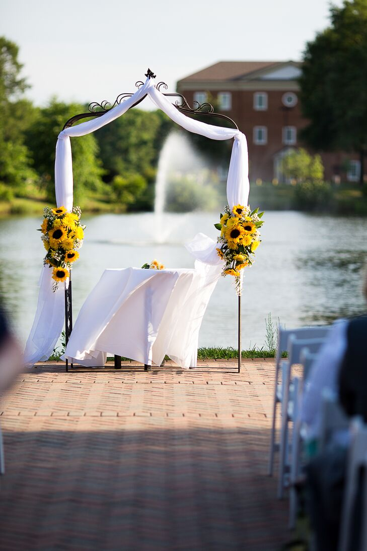 The waterside ceremony at Founders Inn was held under an arch draped with white linen and decorated with bouquets of sunflowers.