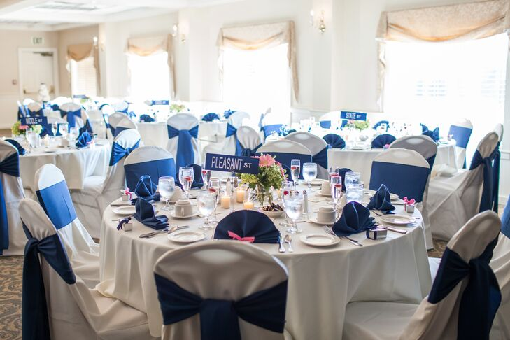 Navy chair sashes and napkins added a pop of color to white tablecloths on the round reception tables.