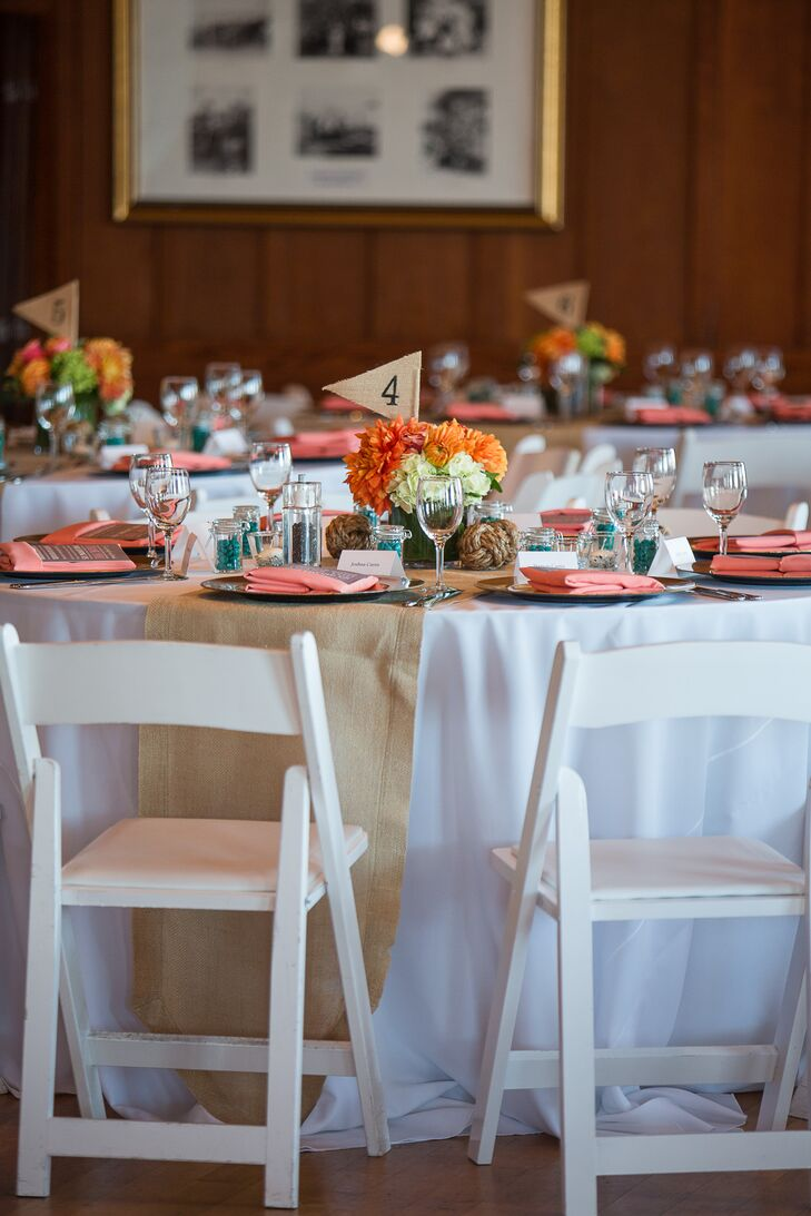 At the reception, guests sat around dining tables covered in white linens. Orange and white flower arrangements decorated the tables, marked with burlap flags that matched the burlap runners draped down the middle.